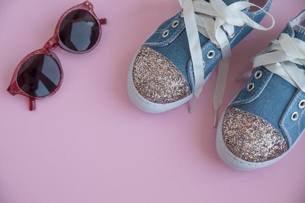 Textile spitzensneaker für kinder. mädchen schuhe an der rosa wand. mode kinderschuhe. smart lässige modische jeans und glänzende schuhe. sonnenbrillen und trendige kinder sportschuhe. kopierraum. selektiver fokus