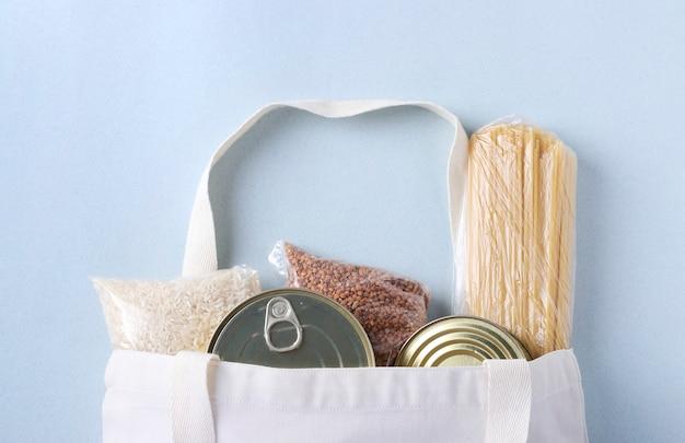 Textileinkaufstasche mit lebensmittelvorräten auf hellblauem hintergrund