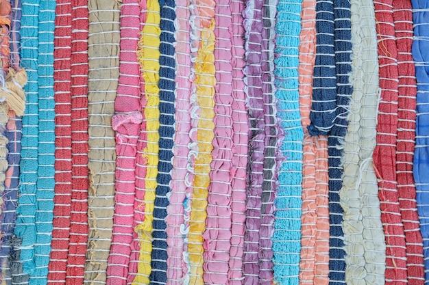 Textiler mehrfarbiger texturhintergrund. nahaufnahme eines aus farbigen fäden gewebten teppichs