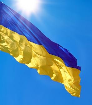 Textilflagge der ukraine entwickelt sich gegen einen klaren blauen himmel