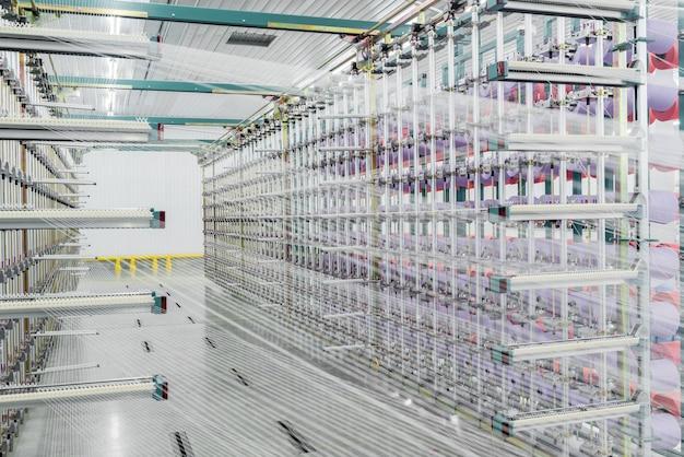 Textilgarn auf der schärmaschine. maschinen und geräte in einer textilfabrik