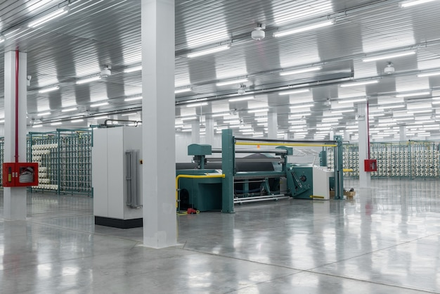 Textilgarn auf der wickelmaschine wird auf die große welle geschraubt ausrüstung in einer textilfabrik
