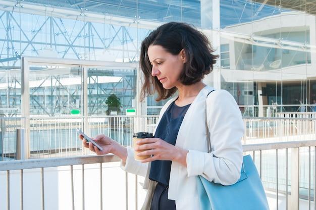 Texting mitteilung der ernsten mittleren erwachsenen geschäftsfrau an der kaffeepause