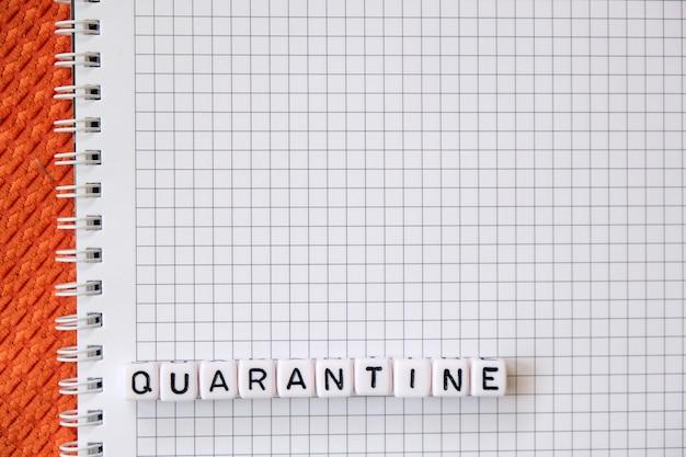 Textquarantäne, wort aus kubischen buchstaben auf einem weißen papiernotizblockhintergrund