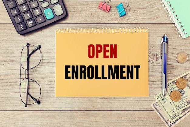 Textschreiben open enrollment rechner, geld und brille auf dem tisch