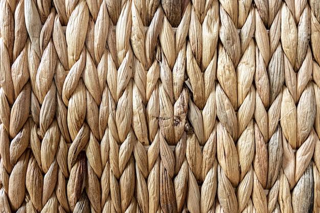 Textur aus gewebtem beigefarbenem stroh, hintergrund von zöpfen aus der nahaufnahme des pflanzenstamms.