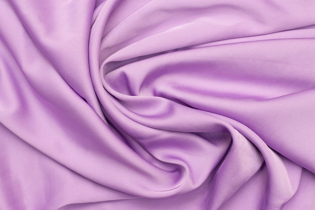 Textur aus seide, lila farbe. schöner luxus. gedrehter glatter, eleganter stoff.
