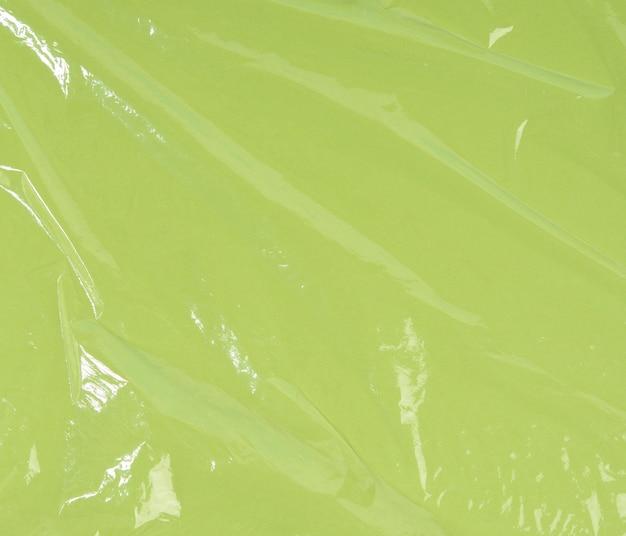 Textur aus zerknittertem transparentem polyethylen auf einer grünen oberfläche, vollrahmen