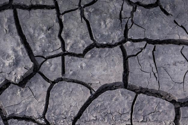 Textur der getrockneten erde. die ausgetrocknete und rissige erde in der wüste, schlamm, sand, zerstörung, schlamm, naturphänomene