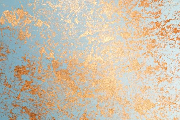 Textur der goldfarbe auf blauem papier