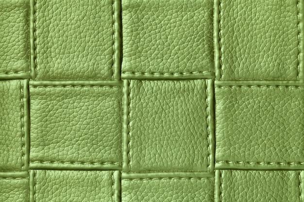Textur der grünen lederoberfläche mit quadratischem muster und stich