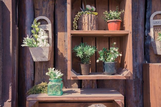 Textur der holzwand mit gartensachen und grünen pflanzen