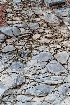 Textur der rissigen wand aus grauem granit