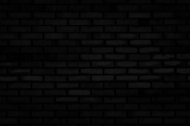 Textur der schwarzen backsteinmauer eines alten hauses.