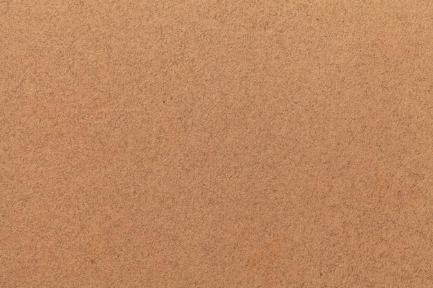 Textur des alten hellbraunen papiers. struktur einer matten dichten papptapete. sand fühlte hintergrund.