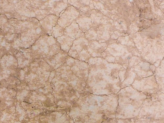 Textur des braunen rissigen trockenen bodens für hintergrund