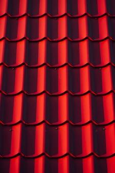 Textur des daches. rote fliese an einem sonnigen tag.