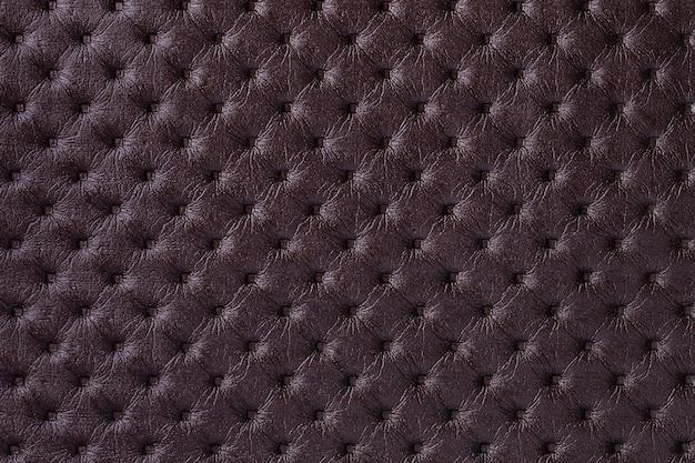 Textur des dunkelbraunen lederhintergrundes mit kapitonmuster, makro. lila textil im retro-chesterfield-stil.