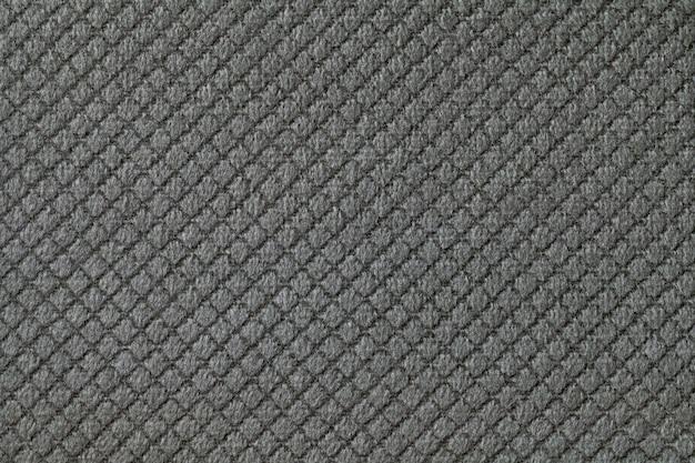 Textur des dunkelgrauen flauschigen stoffhintergrundes mit rhomboidmuster, makro. abstrakter hintergrund aus dekorativem schwarz gewebtem textilmaterial.