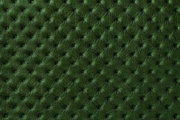 Textur des dunkelgrünen ledergewebehintergrundes mit kapitonmuster. textil im chesterfield-stil.