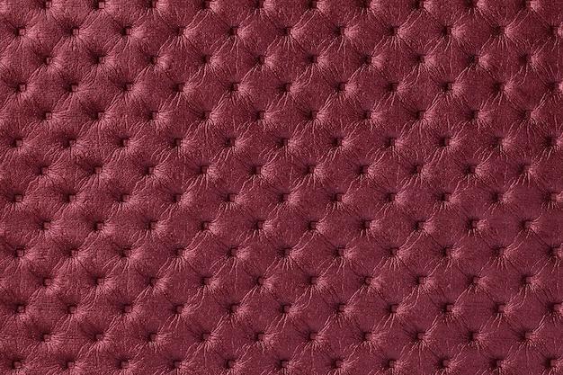 Textur des dunkelroten ledergewebehintergrundes mit kapitonmuster, makro. weintextil im retro-chesterfield-stil.