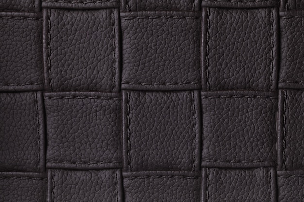 Textur des dunklen schwarzen lederhintergrundes mit quadratischem design und stich, makro.