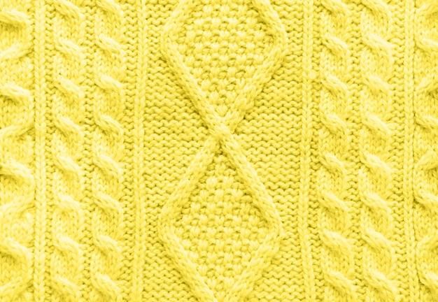Textur des gestrickten handgemachten gelben pullovers