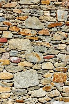 Textur des mauerwerks aus rohsteinen - vertikaler hintergrund