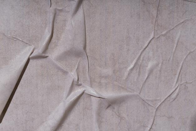 Textur des nassen weißen gefalteten papiers auf einer plakatwand im freien, zerknitterter papierhintergrund.