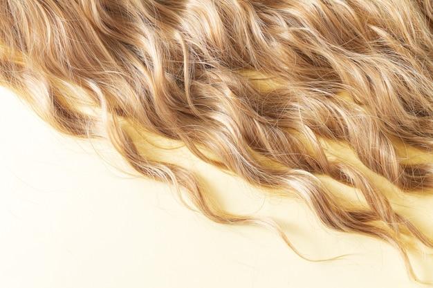 Textur des natürlichen langen blonden gewellten haares. haarschnitt-, styling-, pflege- oder extensionskonzept