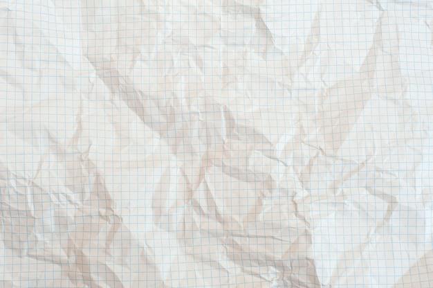 Textur des zerknitterten weißen papiers in einem käfig, schulnotizbuch
