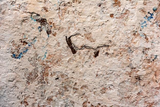 Textur einer betonwand mit rissen und kratzern, die als hintergrund verwendet werden können