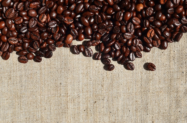 Textur einer grauen leinwand aus alten und groben sackleinen mit kaffeebohnen drauf