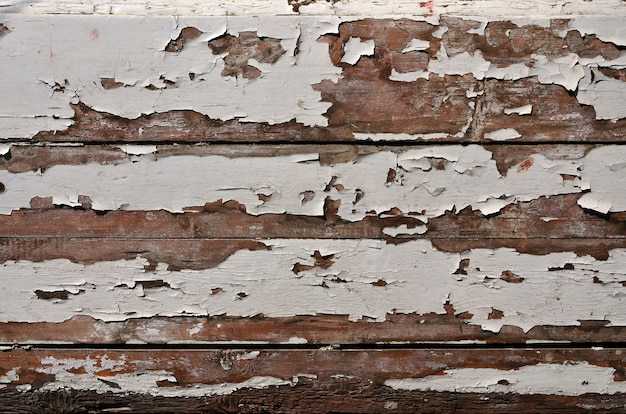 Textur einer holzwand mit einem alten anstrich, der unter dem einfluss von zeit und wetter verderbt