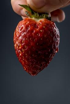 Textur einer nassen erdbeere, die von der hand einer frau auf schwarz gehalten wird