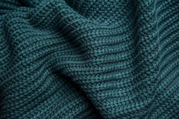 Textur eines grün-blauen wollstrickpullovers