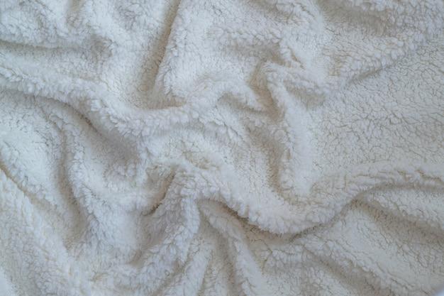 Textur eines weichen plaids. zerknitterte weiße warme decke. stoff zerknittert in falten für hintergrund oder tapete.