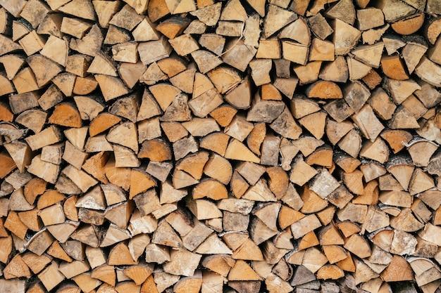 Textur hintergrundbild von gehacktem brennholz in einem holzstapel gestapelt, kopierraum
