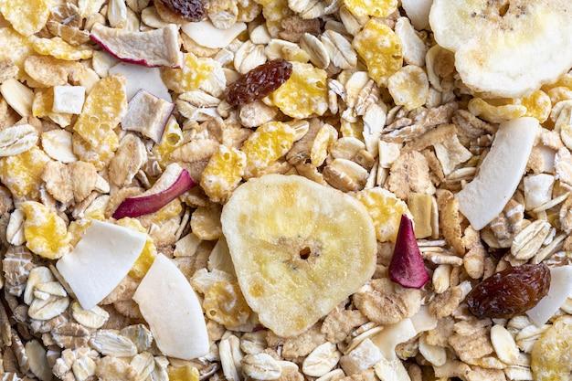 Textur mit vollkornprodukten zum frühstück. makro-nahaufnahme. müsli mit getrockneten früchten und getrockneten früchten. horizontales porträt.