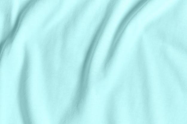 Textur und hintergrund des zerknitterten pastellfarbenen türkisfarbenen stoffes