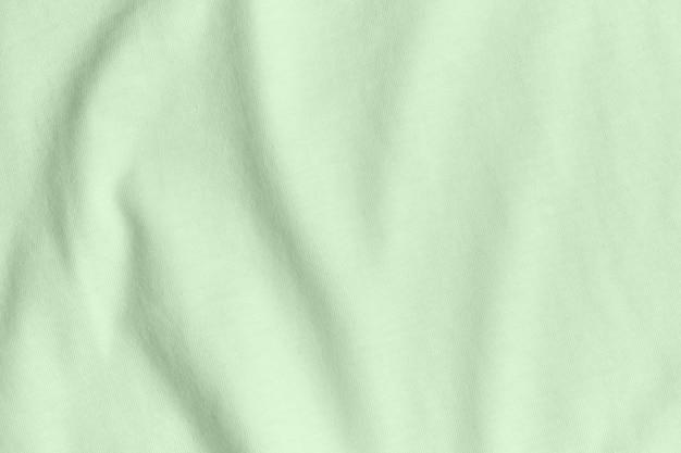 Textur und hintergrund des zerknitterten türkisfarbenen stoffes.