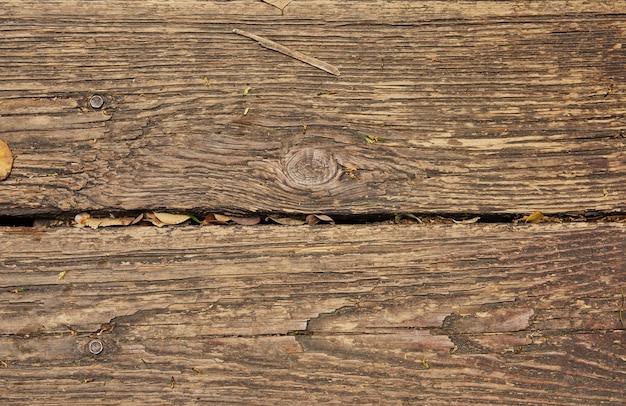 Textur von alten holzbrettern mit gefallenen blättern hintergrund.