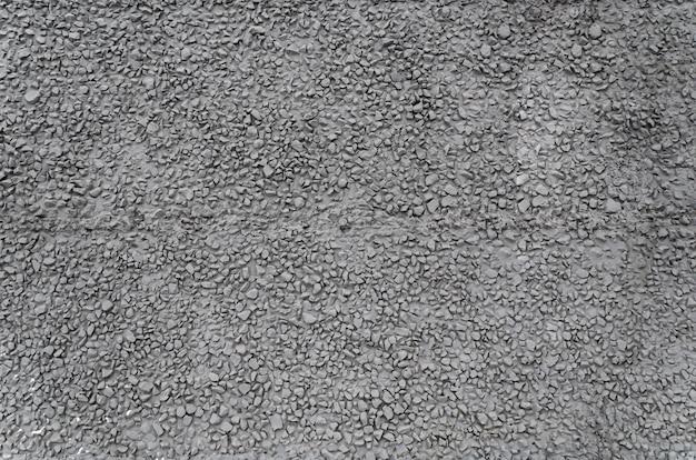 Textur von dunkelgrauem gebäudefassadenzementputz mit feinem kies