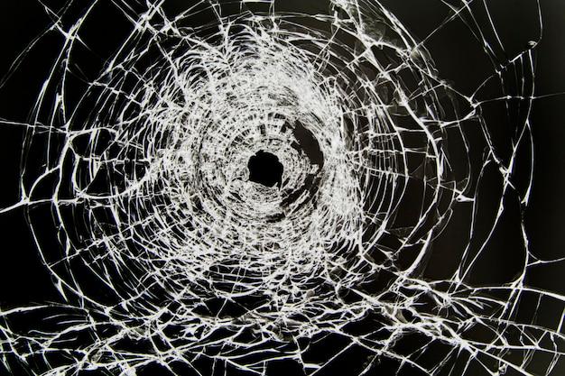Textur von gebrochenem glasscherben mit einem loch, durch aufprall geknackt. konzept schoss im fenster auf einem schwarzen.