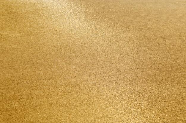 Textur von sand. goldener sand. nasser sand glitzert bei strahlender sonne.