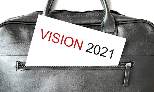 Textvision 2021, die auf weißem papierblatt in der schwarzen geschäftstasche schreibt.