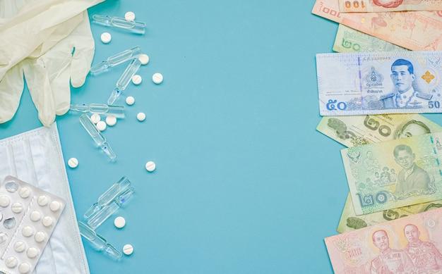 Thai bad banknote und tabletten, ampullen mit medizin, maske