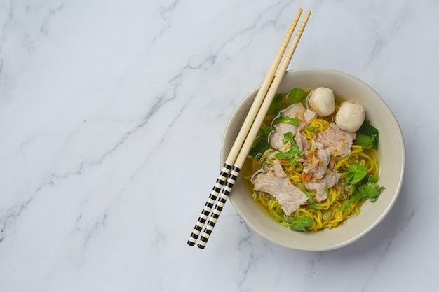 Thai essen. nudeln mit schweinefleisch, fleischbällchen und gemüse