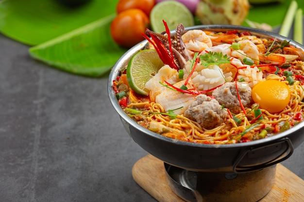 Thai essen. nudeln würzig kochen mit meeresfrüchten und schweinefleisch im heißen topf
