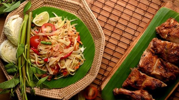 Thai-food-papaya-salat somtum mit gegrilltem hühnchen im thailändischen stil im thailändischen restaurant-draufsicht
